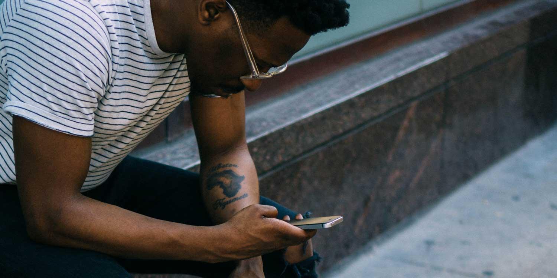 man looking at phone on sidewalk