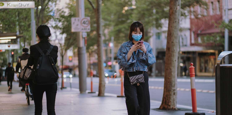 masked woman walking phone